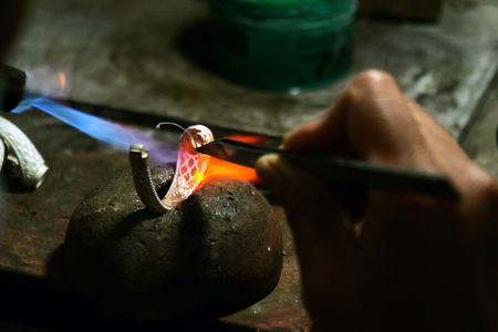 Close-up of a goldsmith who builds a precious jewel with valuable diamonds. It takes: precision, craftsmanship and patience. Concept of: gold, luxury.