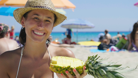 Holding a pineapple in a swimsuit in a straw hat, beach background. Concept: sea rest, clean air, freedom, sun, travel, enjoy, fresh fruit, vacation.