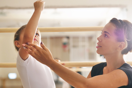 A teacher of classical dance teaches some steps to a young student who wants to learn how to dance. Concept of: ambition, education, teaching and love for the dance