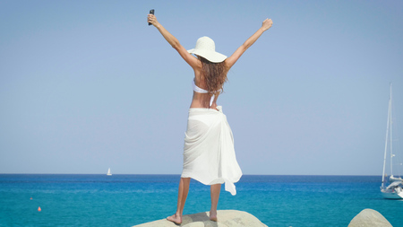 A beautiful young woman smiling, feels happy, in a hat, sunglasses, on a blue background. Concept: sea rest, sun, travel, vacation, freedom