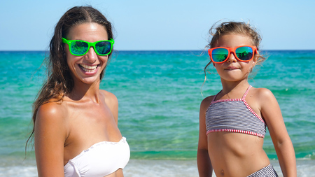 Mother and little daughter playing on the sea, wearing sunglasses, smiling in bathing suits.