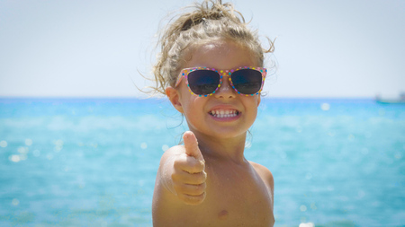 Portrait of a beautiful young woman with sunglasses on the beach. Concept: children, childhood, summer time, freedom, kids, daughter, baby, smile.