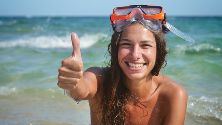 Beautiful young woman in a swimsuit wearing a diving mask.