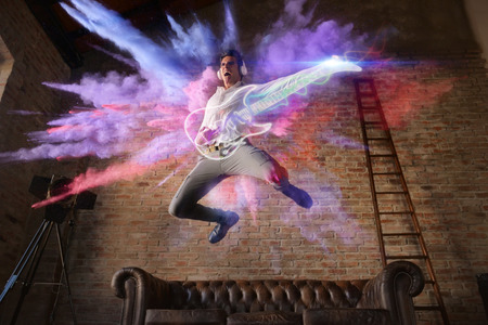 man jumps with colorful background playing a virtual guitar. concept of freedom and creativity with music