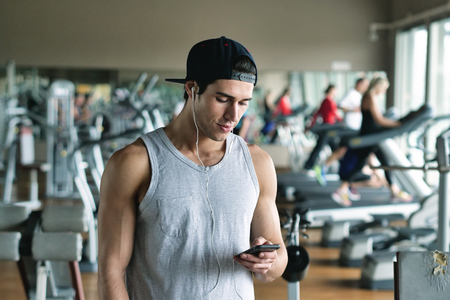 With a man getting ready for his workout and putting some music on his headphones. Concept of: sport, personal trainer and fitness and music 版權商用圖片