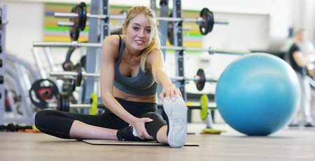 A young beautiful girl in a gym, leaning on her hands, shakes the press, making long steps, bending her knees. Concept: to love sports, to attend a gym, proper nutrition, a slender body, to be healthy