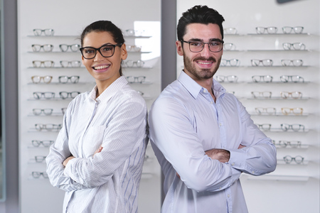 A vision of a pair of ophthalmologists, who makes eye-ophthalmological for a client in an optical center. Try the spectacles to the patient. Concept of: medical examination, assistance, optics Banco de Imagens