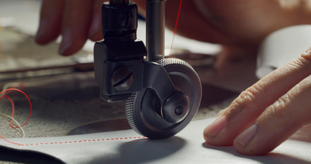 Close up of a shoemaker sewing with red leather Concept: handmade, fashion, industrial, factory. 免版税图像