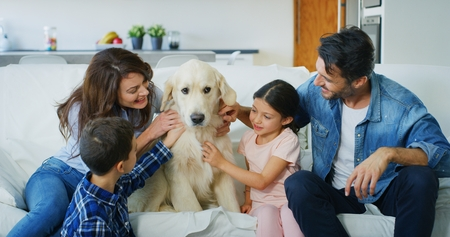 Portrait of a happy family in a living room. Concept of happy family, love for animals, childhood Archivio Fotografico - 118558094