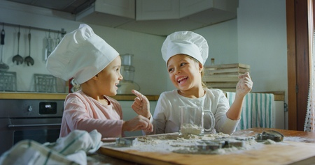 Two little girls in the kitchen prepare food, a dessert for the family. They start to cook and start each other. Concept of: cooking classes, family, education. Banco de Imagens