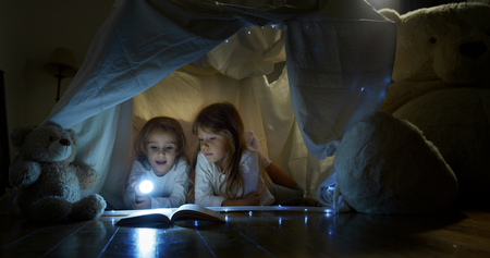 Two little girls sisters (kids) read stories in the dark under the light illuminating with a torch. Concept: Love, Family, Dreams