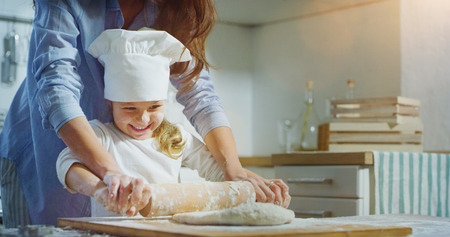 A mother and a daughter play and have fun in the kitchen while cooking together. Concept: Happiness, family, holiday Banco de Imagens
