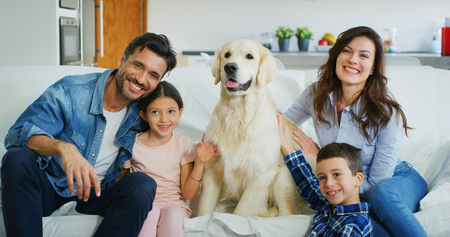 Portrait of a happy family in a living room. Concept of happy family, love for animals, childhood