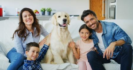 Retrato de una familia feliz en una sala de estar. Concepto de familia feliz, amor por los animales, infancia Foto de archivo