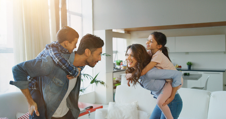 Portrait of happy family having fun in slow motion on kitchen. Concept of happy family, childhood, parenthood Banco de Imagens