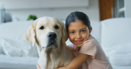 Portrait of a little girl playing and cuddling her dog in living room. Concept of love for animals, childhood, pedigree dog