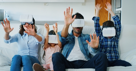 Portrait of happy family using vr glasses in living room in slow motion. Concept of innovation technology, family entertainment, game Banco de Imagens