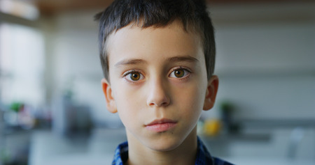 Close up portrait of a little boy with brown eyes looking in the camera on kitchen background. Concept of childhood, youth, kids protection, son, happy family