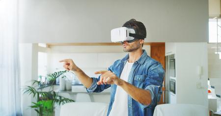 Portrait of handsome man using vr glasses in living room. Concept of innovation technology, lifestyle, entertainment. Banco de Imagens