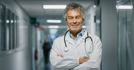 Portrait of a smiling doctor with a job in a corridor of a hospital. Concept of medicine, technology, health care and people, hospital Banco de Imagens