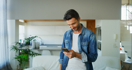 Portrait of a handsome middle aged man using smart phone in living room. Concept of lifestyle, technology, connection, internet, social media