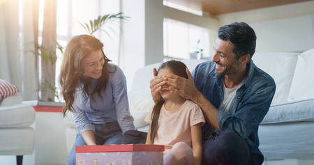 Portrait of happy family having fun in living room in slow motion. Concept of surprise present, birthday gift, happy family, childhood, parenthood