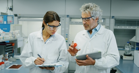 Portrait of two scientists testing the laboratory. Concept: research, biochemistry, pharmaceutical medicine Banco de Imagens
