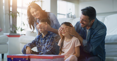 Portrait of happy family having fun in living room in slow motion. Shot with RED camera in 8K. Concept of surprise present, birthday gift, happy family, childhood, parenthood Banco de Imagens