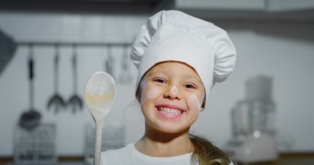 Portrait of a little girl in a kitchen. Concept of: nutrition, cooking school, education. Banco de Imagens
