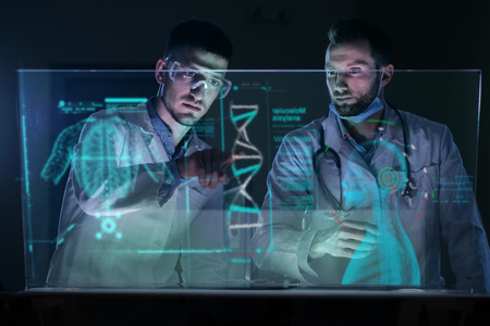 A couple of doctors or scientists analyze the patients medical situation. Concept of: medicine, doctors, future, holography. Banco de Imagens