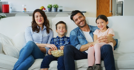 Portrait of happy family watching TV on sofa in living room in slow motion. Concept of family entertainment, education, technology. Banco de Imagens