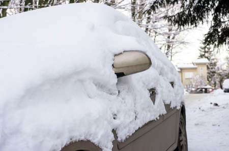 car under snow during storm winter weather