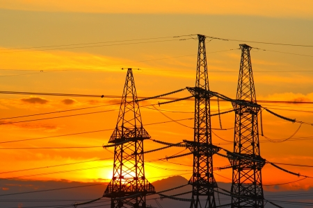 High-voltage support against the sunset sky