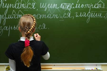 Het schoolmeisje schrijft krijt op een schoolbord