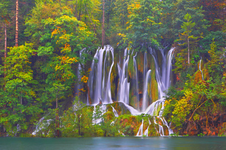 Autumn landscape background. Plitvice Lakes. Croatia. Falls in the autumn wood. photo