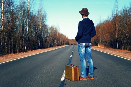 in jeans: Viaje a las vacaciones. Viaje a un hombre de semana end.The en pantalones vaqueros con una maleta.