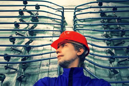 De werknemer in een helm op factory.Industrial interieur.