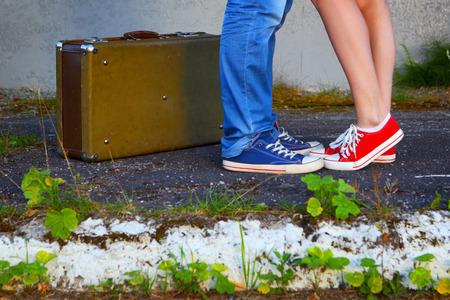 Jonge couple.Romantic meeting.Suitcase, jeans en sneakers.The foto getint is in een retro stijl.