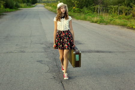 Summer vacation with a suitcase. A girl travels on foot.Photo tinted and styled with vintage photo.