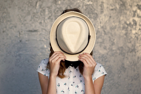 summer clothing: Young girl with hat. Hides her face.Depression.Photo tinted and styled with vintage photo.