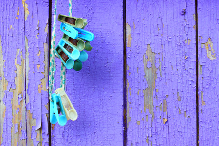 clothespeg: Clothespins against a wooden wall. House utensils.