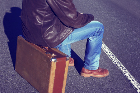 emigration: Emigration, resettlement, refugee, migration.The man in jeans with a suitcase.Photo toned in retro style.