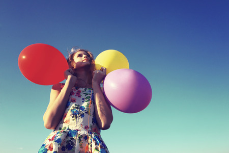 shyness: The girl covers her face with balloons. Shyness, shame, resentment.Photo toned in retro style. Stock Photo