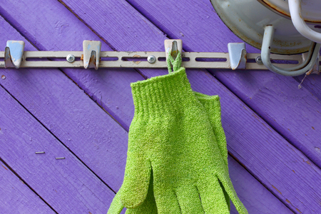 Green gloves against violet boards. A hanger on a wall of the private house. abstract symbol Stock Photo