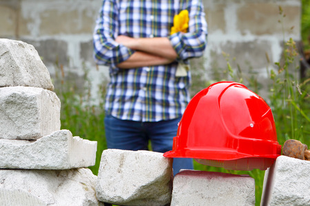 Builder in a plaid shirt. Helmet and stonework.