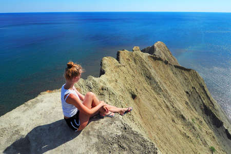 A young lady is sunbathing on a high beach. Crimea. Cape Chameleon. Vacation on the sea coast in the warm summer season Standard-Bild