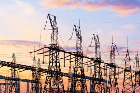 Electrical substation. Power lines against the sunset sky. Production and transmission of electricity in industry