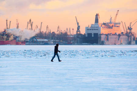 Winter. Urban landscape. A man walks on ice in background of the seaport