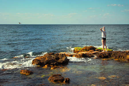 Girl by the sea. A young lady stands on a stone bank. Seascape. Photo tinted in retro style. Standard-Bild