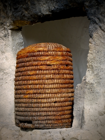 apiary: Straw bee hive in stone window
